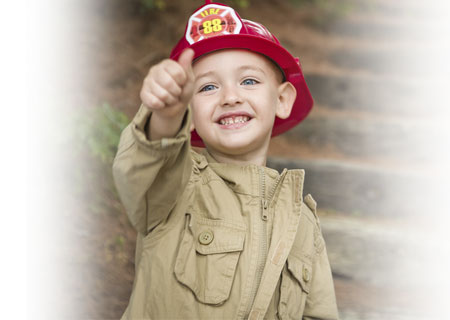 Young boy wearing firefighter helmet